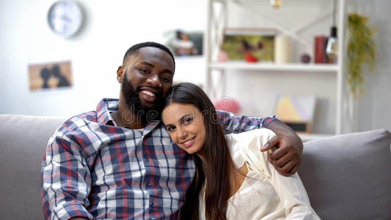 拥抱和看照相机的愉快的不同种族的夫妇,一起放松 免版税库存图片