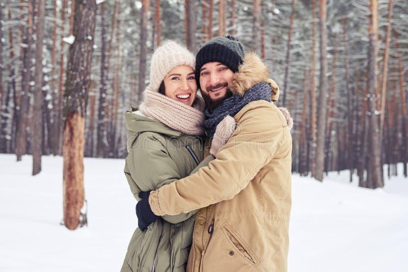 拥抱和看的微笑的夫妇照相机whil 免版税图库摄影