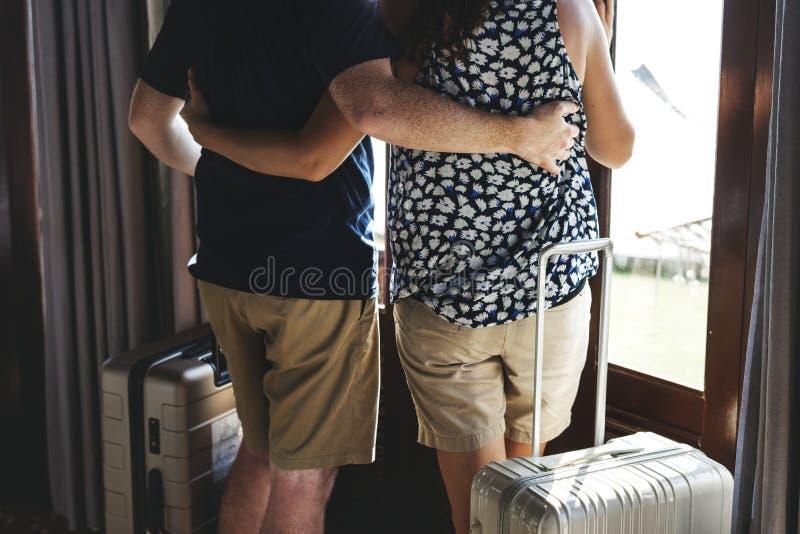拥抱和站立与行李的夫妇 免版税库存照片