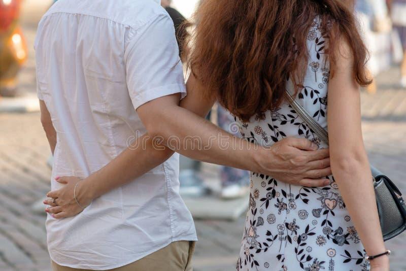 拥抱和走在城市,后面看法的爱恋的夫妇 免版税库存照片
