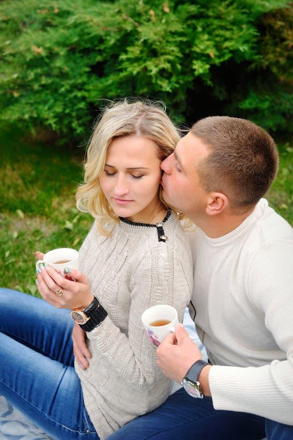 拥抱在一条毯子下的年轻美好的夫妇在公园 库存照片
