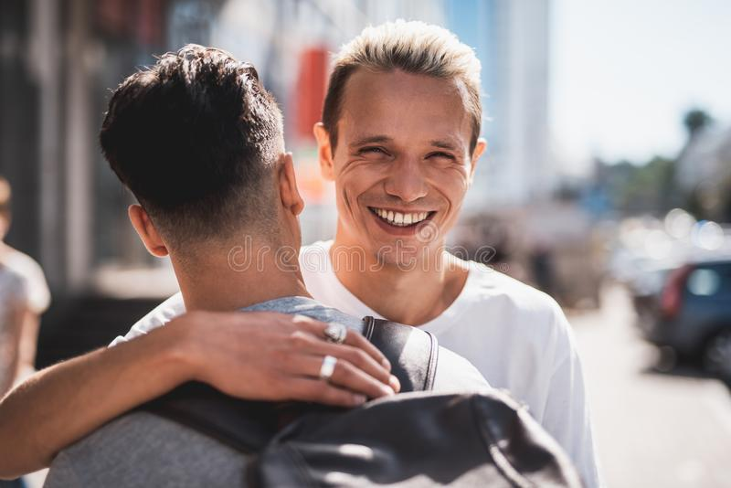 拥抱在会议期间的满意的朋友在街道 库存图片