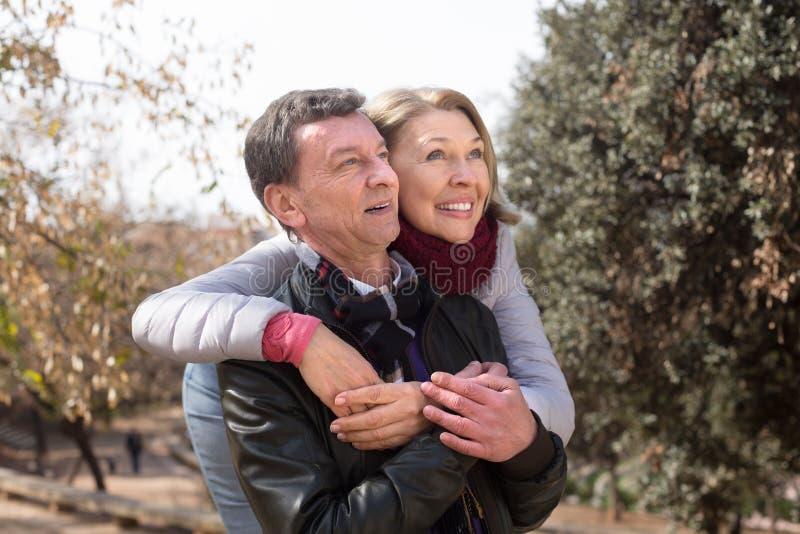 拥抱在公园的微笑的成熟家庭夫妇 免版税库存照片