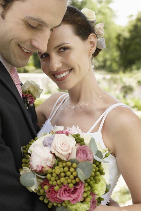 拥抱在公园的新娘和新郎 免版税库存图片