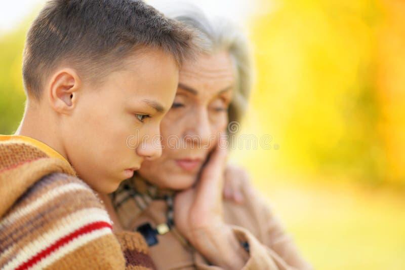 拥抱在公园的祖母和孙子画象  免版税库存图片