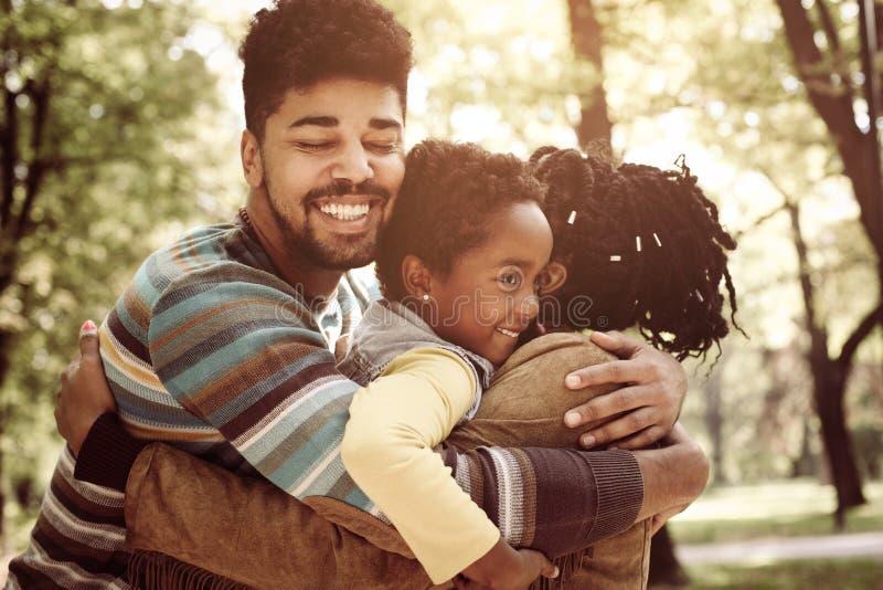 拥抱在公园的非裔美国人的家庭 免版税库存照片