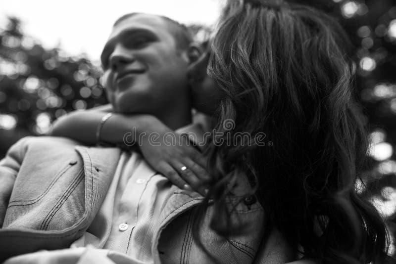 拥抱在公园长椅的年轻欧洲夫妇 库存照片