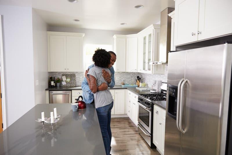 拥抱在公寓厨房里的年轻夫妇 库存图片