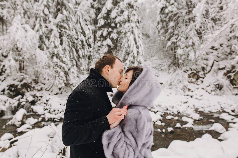 拥抱在冬天多雪的山的时髦的夫妇 愉快romant 免版税库存图片