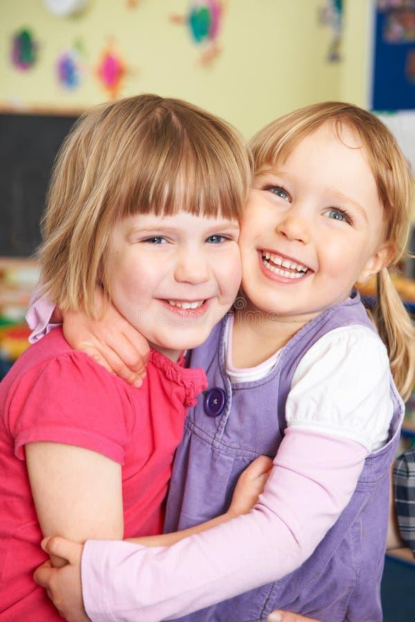 拥抱在前学校的两个女孩 图库摄影