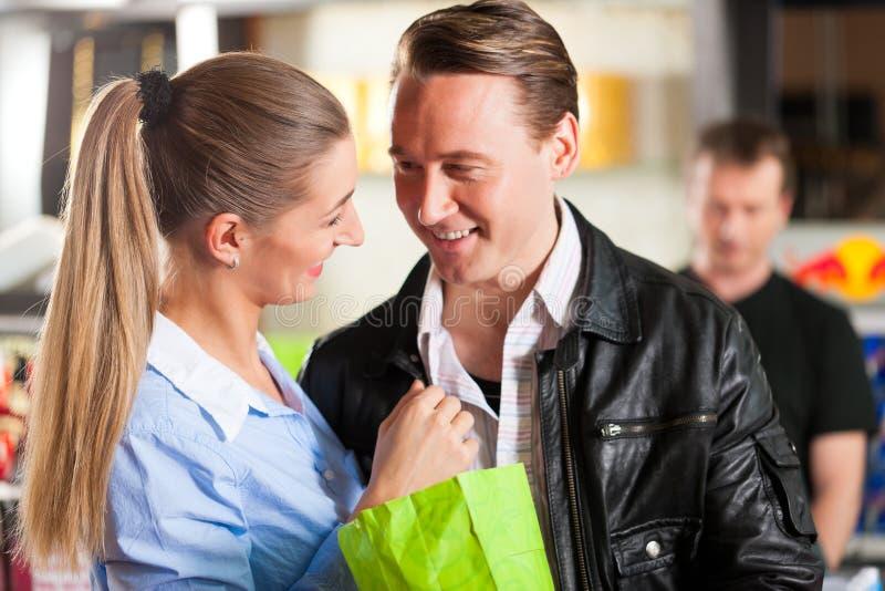拥抱在剧院的夫妇买的玉米花 免版税库存图片