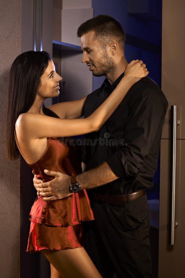 拥抱在卧室门的新夫妇 免版税图库摄影