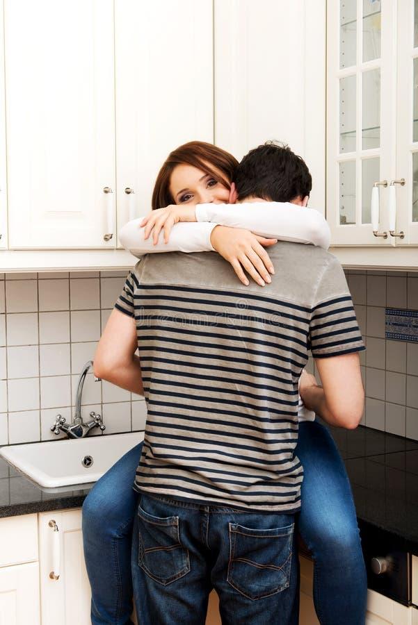 拥抱在厨房里的浪漫夫妇 免版税图库摄影