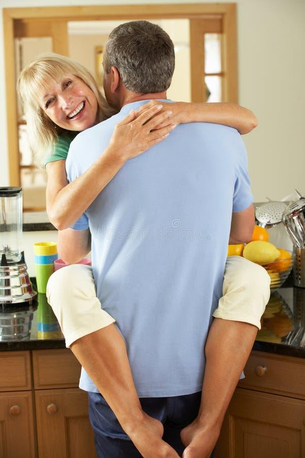 拥抱在厨房里的浪漫高级夫妇 库存照片