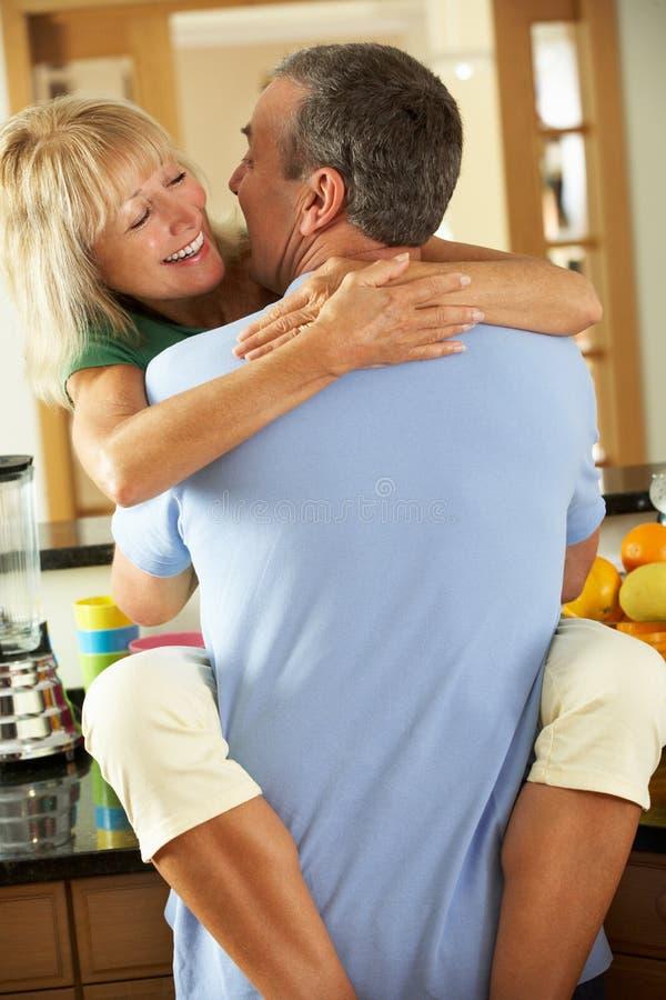 拥抱在厨房里的浪漫高级夫妇 免版税库存照片