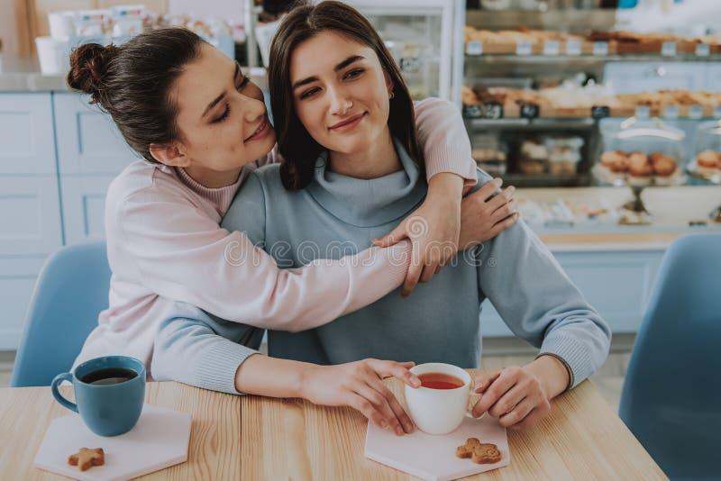拥抱在咖啡馆的宜人的女性朋友 库存照片