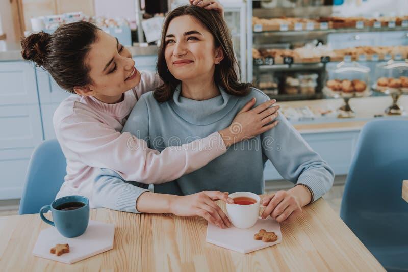 拥抱在咖啡馆的快乐的女性朋友 库存图片