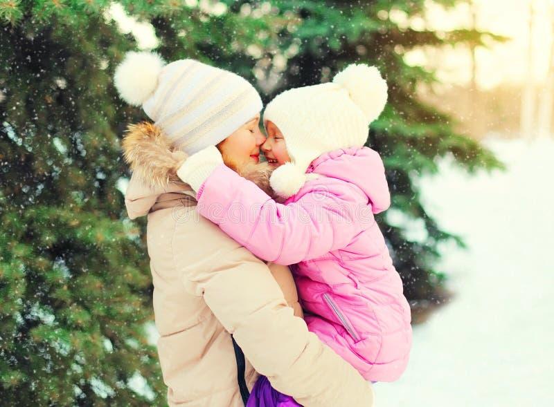 拥抱在圣诞树雪花的冬天愉快的母亲孩子 免版税库存照片