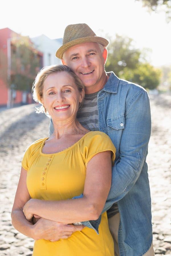 拥抱在城市的愉快的成熟夫妇 免版税库存图片