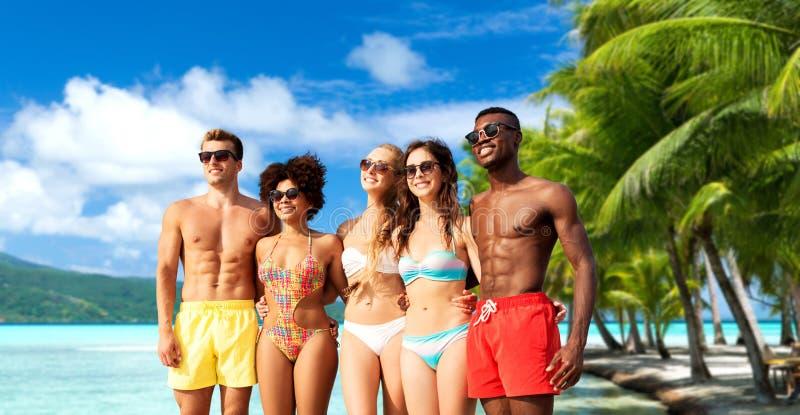 拥抱在夏天海滩的游泳衣的愉快的朋友 免版税图库摄影