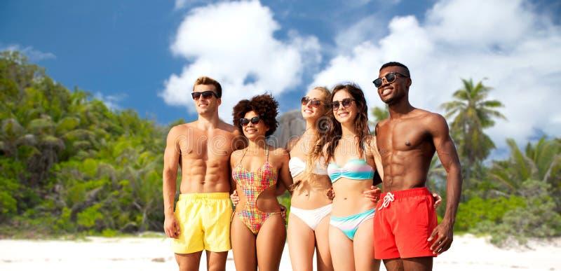拥抱在夏天海滩的游泳衣的愉快的朋友 免版税库存照片