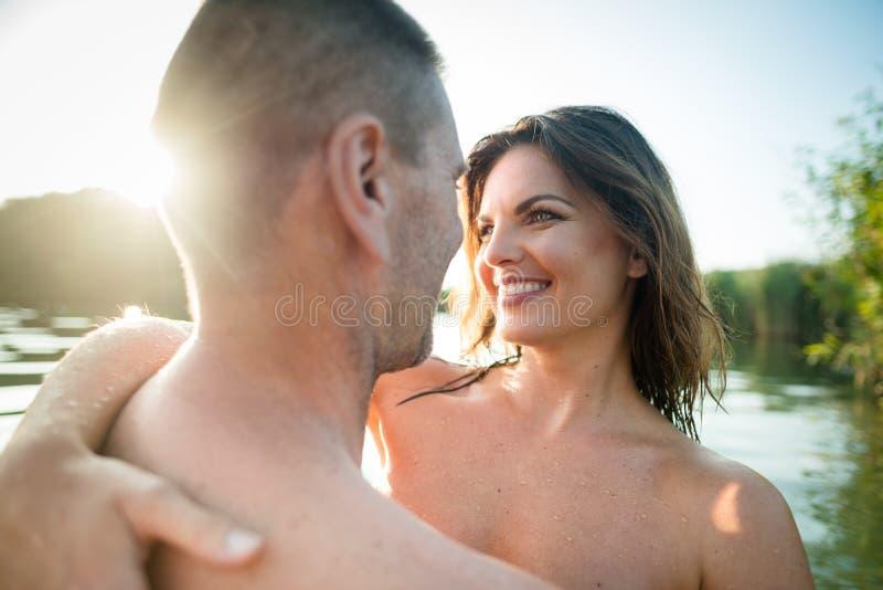 拥抱在夏天湖的富感情的裸体夫妇 免版税库存图片