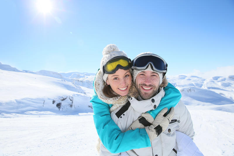 拥抱在多雪的山的夫妇 库存图片