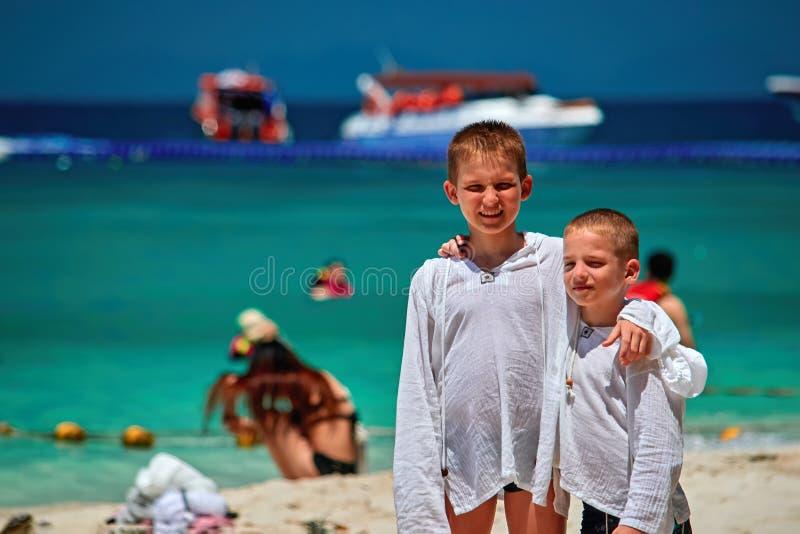 拥抱在天堂海滩的两个兄弟立场 孩子在衬衣打扮保护免受紫外 愉快的微笑的男孩 库存照片