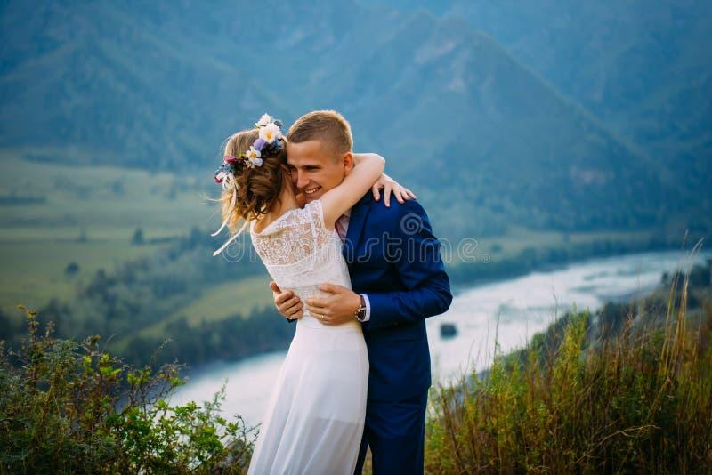 拥抱在岩石顶部的愉快的新婚佳偶夫妇有山背景  免版税库存图片