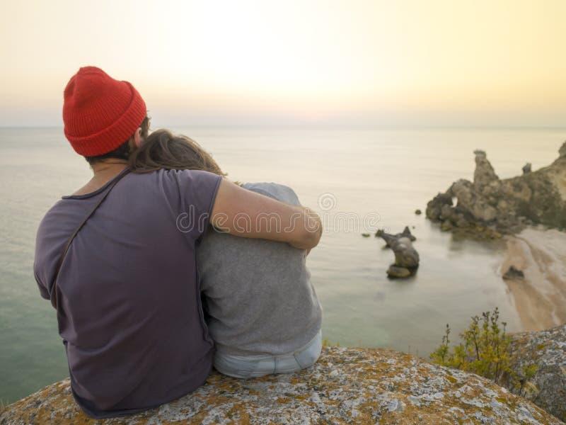 拥抱在峭壁的浪漫年轻无忧无虑的夫妇在日落期间 后面观点的妇女和人户外爱的在海附近 免版税库存图片
