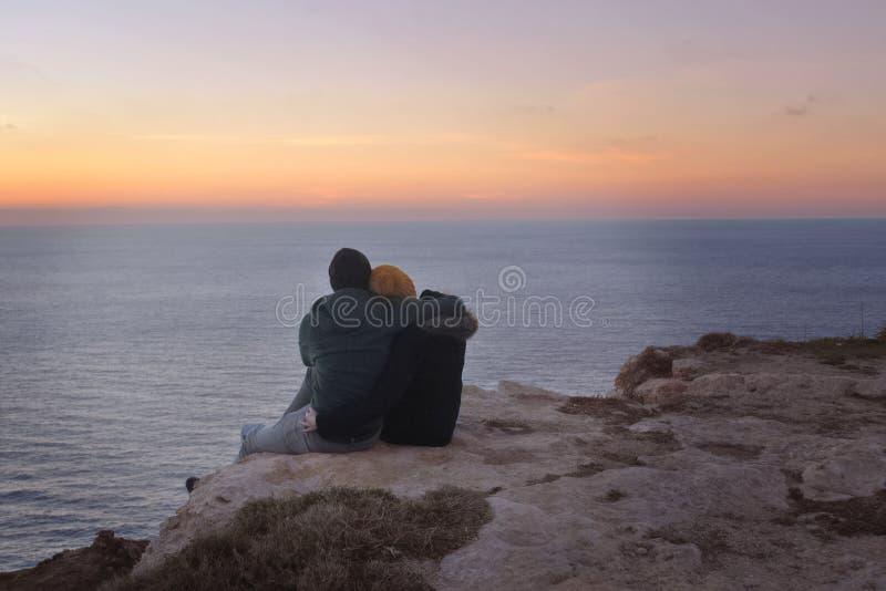 拥抱在峭壁的年轻夫妇在日落 免版税库存照片