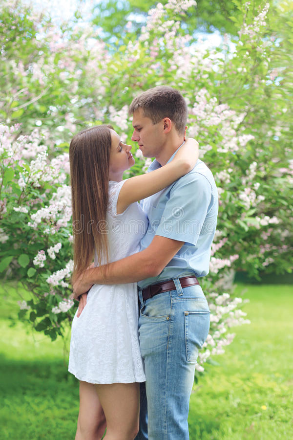 拥抱在开花的庭院里的美好的年轻爱恋的夫妇 免版税库存图片