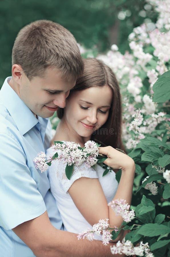 拥抱在开花的庭院里的画象美好的年轻爱恋的夫妇 库存照片