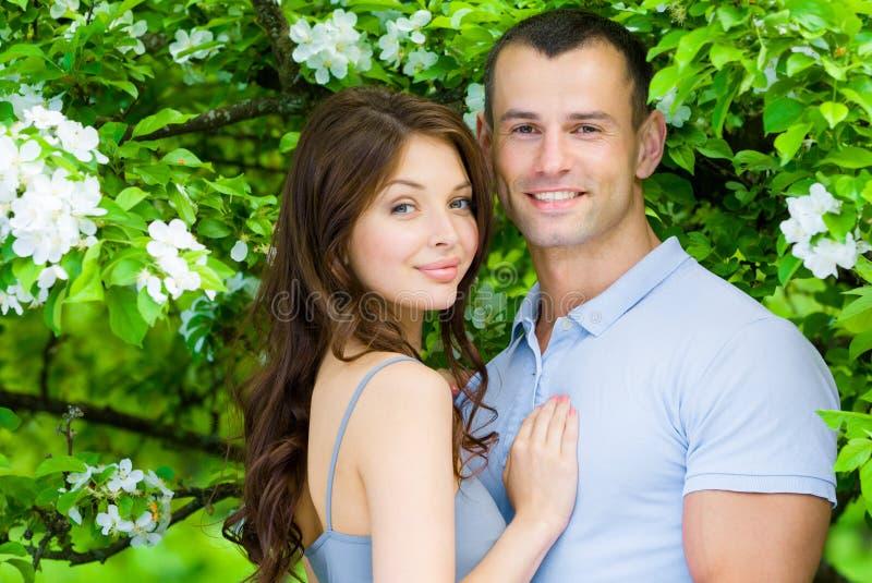 拥抱在开花的树附近的美好的夫妇 库存图片