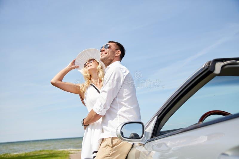 拥抱在敞蓬车汽车附近的愉快的夫妇海上 库存照片