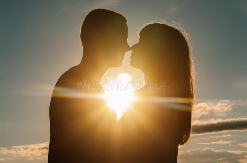 拥抱在日落的爱恋的夫妇剪影  库存图片