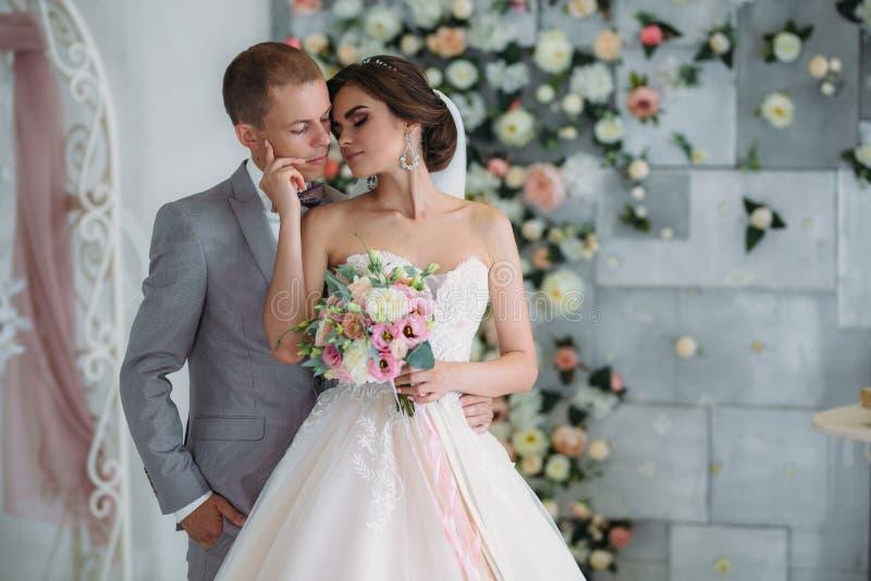 拥抱在明亮的演播室的美好的婚礼夫妇 企业灰色衣服的新郎,在蝶形领结的一件白色衬衣和a 免版税库存照片