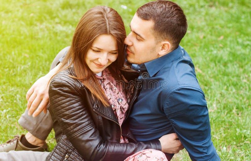 拥抱在春天绿色公园的美好的浪漫夫妇 免版税图库摄影