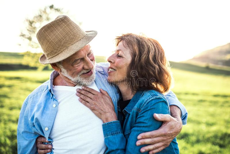 拥抱在春天自然的资深夫妇外部 库存照片
