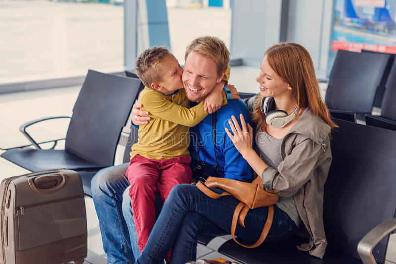拥抱在机场的愉快的家庭 免版税库存照片