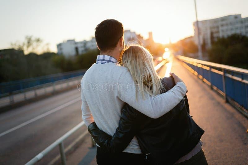 拥抱在桥梁的愉快的年轻有吸引力的夫妇 免版税图库摄影