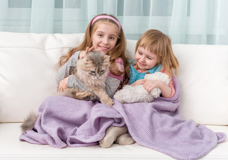 拥抱在沙发的两个可爱的小女孩 免版税库存照片