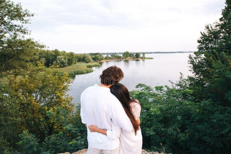 拥抱在河背景的夫妇在叶子附近 免版税库存照片