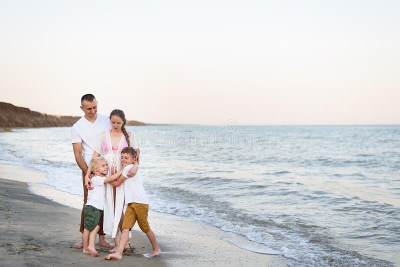 拥抱在沿海父母、怀孕的母亲和两个儿子的幸福家庭四 库存照片