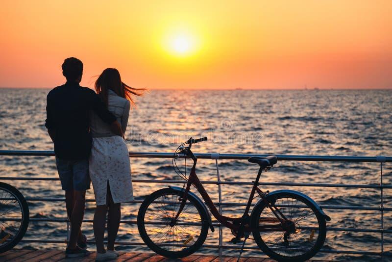 拥抱在海滩和观看日出的年轻行家恋人夫妇在木甲板夏时 免版税库存图片
