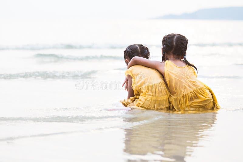拥抱在海滩的后面观点的两个逗人喜爱的亚裔小孩女孩 免版税库存照片