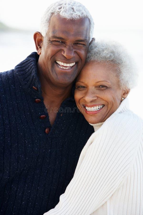 拥抱在海滩的浪漫高级夫妇 免版税图库摄影