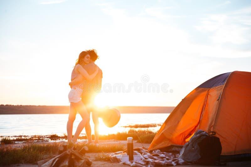 拥抱在海边的一对愉快的年轻夫妇的画象 免版税库存图片