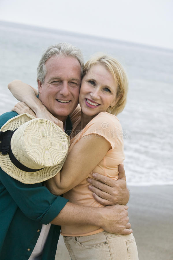 拥抱在海滩和看照相机的中年夫妇 免版税库存照片