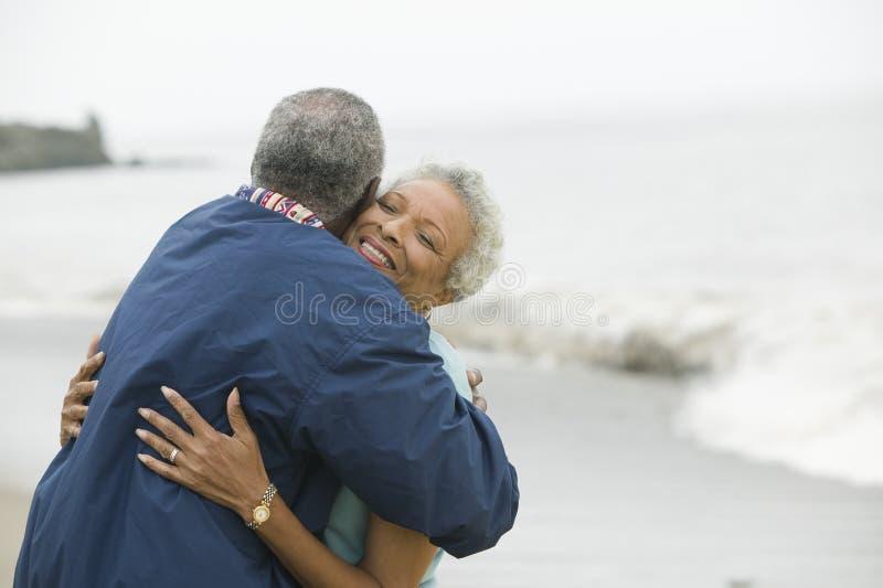 拥抱在海滩的中年夫妇 库存图片